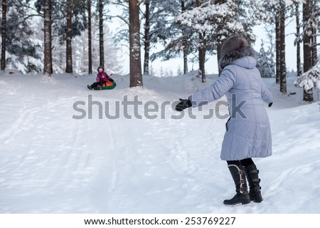Woman catching child tubing on downhill in winter forest - stock photo