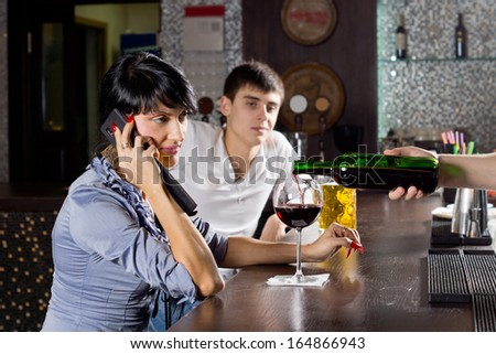 Woman chatting on her mobile while drinking at the bar in a pub sitting sideways at the counter listening to the conversation while the barman pours her another drink - stock photo
