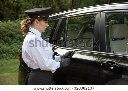 Woman chauffeur using a key flob to open the car door - stock photo