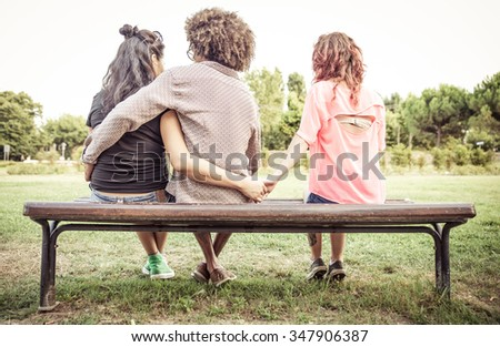 Woman cheating on her boyfriend with an other girl at the park. concept about relationships - stock photo