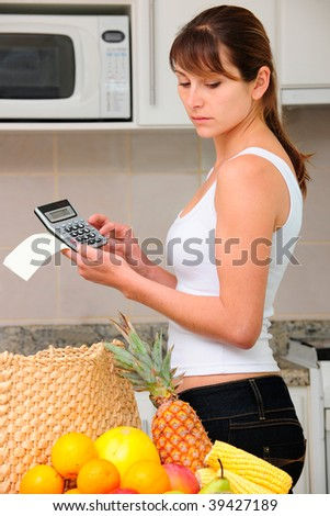 woman checking bill with calculator in the kitchen - stock photo