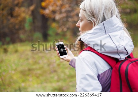 Woman checking compass app on her smartphone - stock photo