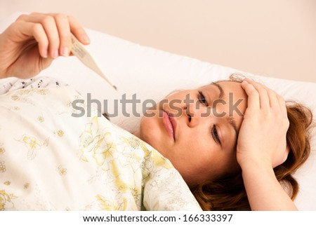 woman checking fever with digital termomether girl with flu resting in bed - stock photo