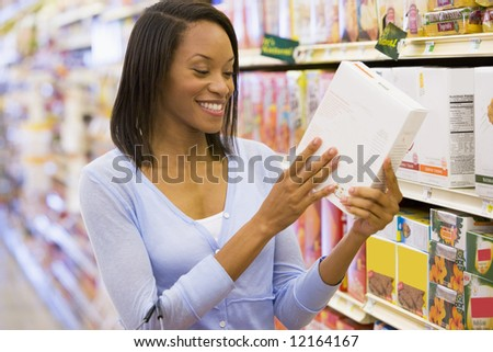 Woman checking food labelling on packet in supermarket - stock photo
