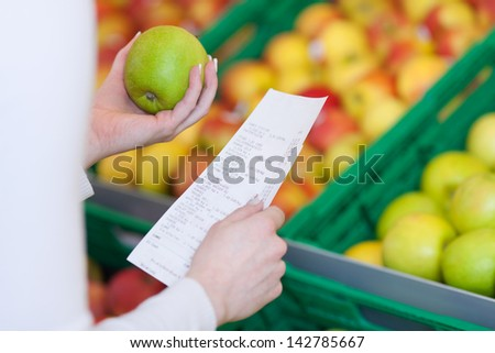 Woman checking her till slip or receipt when shopping for fresh fruit in a supermarket holding a green apple in her hand - stock photo