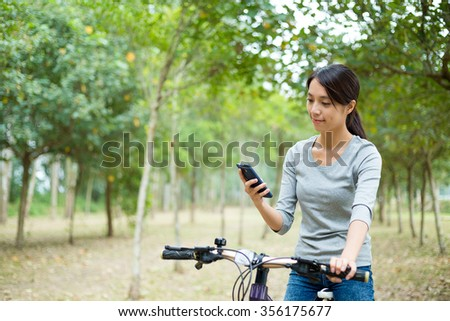 Woman checking the GPS on mobile phone when cycling - stock photo