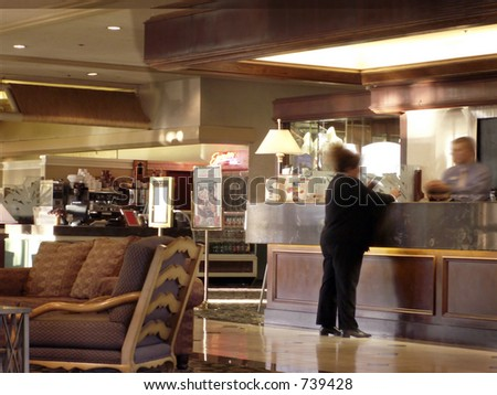 Woman checks in at hotel desk with desk clerk -- coffee bar at back. - stock photo
