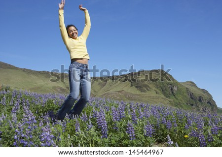 Woman cheering in meadow  - stock photo