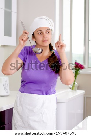 Woman chef having a brainwave as she tastes the food in the saucepan from a ladle raising her finger as she thinks of a new or missing ingredient - stock photo
