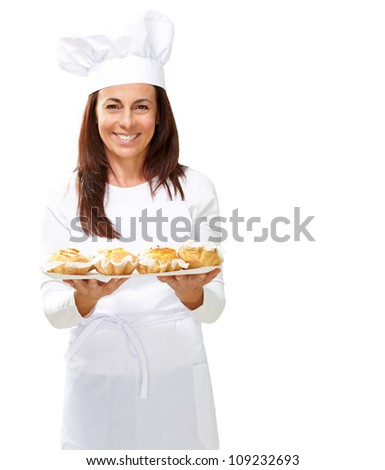 Woman chef holding baked food on white background - stock photo