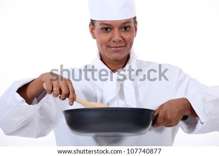 Woman chef stirring a wok - stock photo