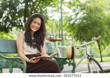 Woman chilling in the park with her book and her bicycle - stock photo
