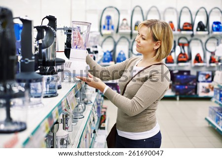 Woman chooses a blender in the store - stock photo