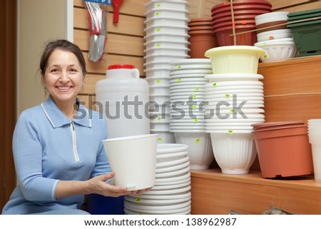 Woman chooses flowerpot in the store for gardeners - stock photo