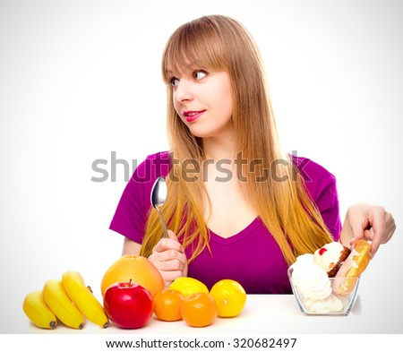 woman choosing between fruit and sweets , isolated over white - stock photo
