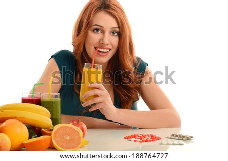 Woman choosing between pills and an organic smoothie, choosing from vitamin pills and healthy natural juice - stock photo