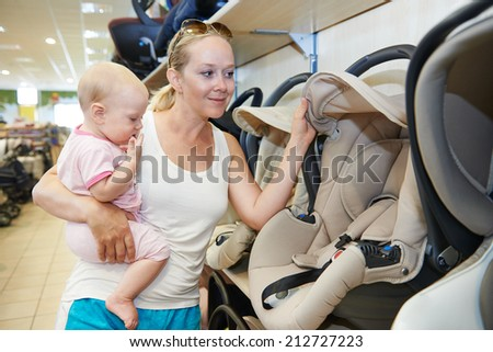 woman choosing child car seat with little baby in shop supermarket - stock photo