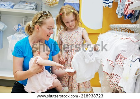 woman choosing children apparel with little baby child and girl on hands in clothing shop supermarket - stock photo