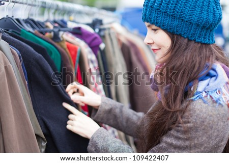 Woman choosing clothes at flea market - stock photo