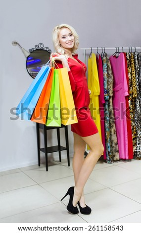 Woman choosing dress to wear in the shopping mall. Full Shopping Bags. Sales - stock photo