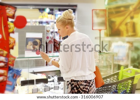 Woman choosing  food from a supermarket freezer. Checking list. - stock photo