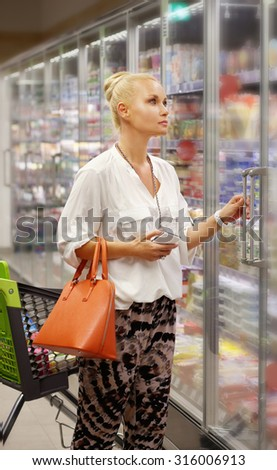 Woman choosing frozen food from a supermarket freezer. Checking list. - stock photo