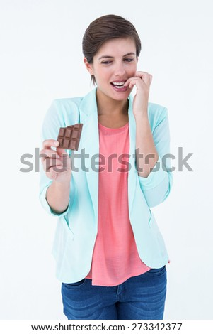Woman choosing to eat chocolate or not on white background - stock photo