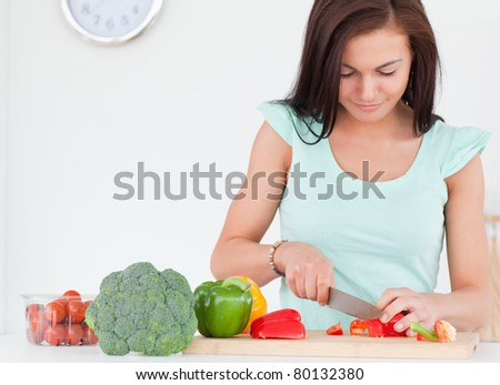 Woman chopping vegetables in her kitchen - stock photo
