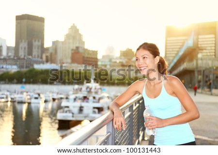 Woman city runner resting after running workout. Female fitness model smiling happy drinking water enjoying a break. Beautiful fit mixed race Asian Chinese and Caucasian woman outdoors. - stock photo