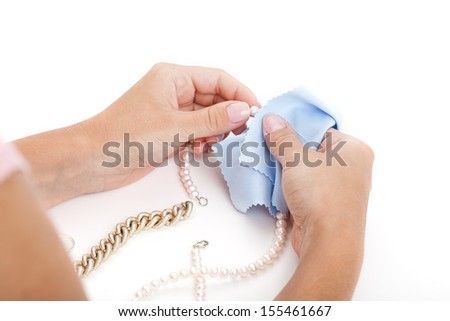 Woman cleaning a jewellery with a special cloth - stock photo