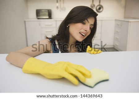 Woman cleaning a kitchen counter - stock photo