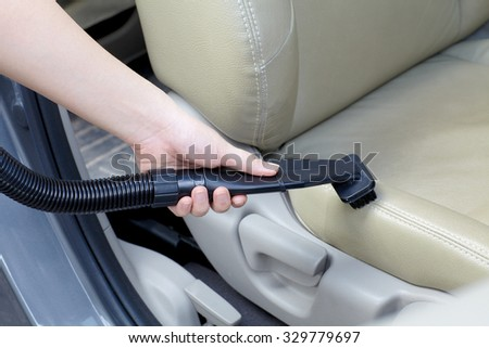 Woman cleaning car seat with vacuum cleaner - stock photo