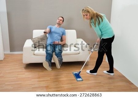 Woman Cleaning Floor With Mop While Man Sitting On Sofa - stock photo