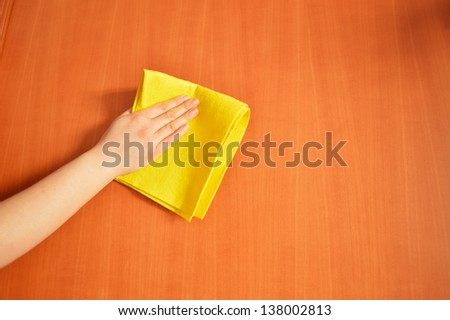 woman cleaning furniture  with yellow cloth - stock photo