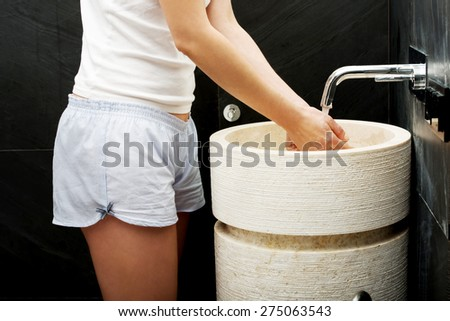Woman cleaning hands in bathroom. - stock photo