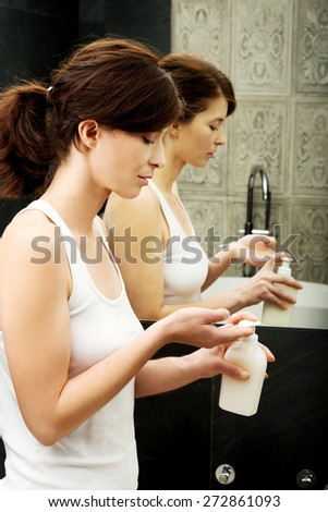 Woman cleaning hands with soap in bathroom. - stock photo