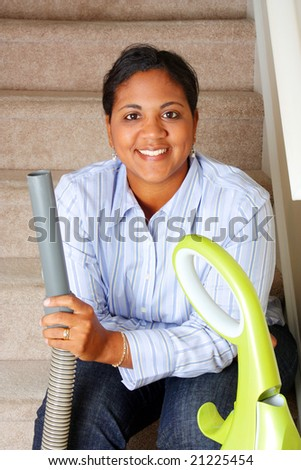 Woman cleaning in her house with a vacuum cleaner - stock photo