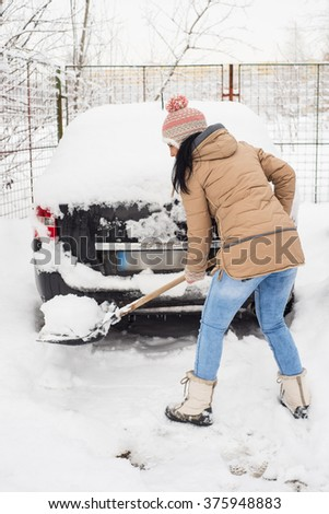 Woman cleaning snow around car and making a path - stock photo