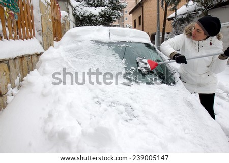 Woman cleaning snow from the car - stock photo