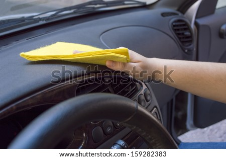 woman cleaning the car interior with yellow cloth - stock photo