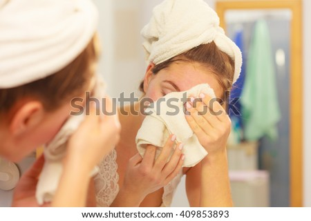 Woman cleaning washing her face with clean water in bathroom. Girl taking care of her complexion. Morning hygiene. Skincare treatment - stock photo