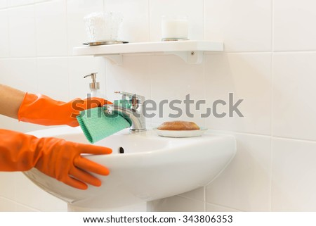 Woman cleaning water tap witn orange glove - stock photo
