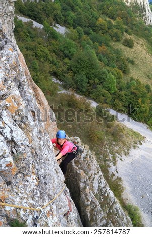 Woman climber hanging on the rock wall high above ground - stock photo