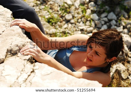 woman climbing a boulder - stock photo