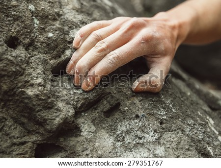 Woman climbing on rock outdoor, close-up image of climber hand in magnesium powder - stock photo