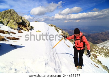 Woman climbs a snow covered slope with an ice axe - stock photo