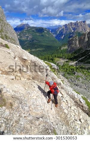 Woman climbs along Durissini trail in Cadini di Misurina, Dolomite Alps, Italy - stock photo