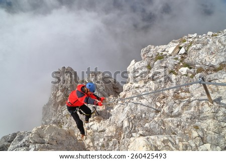 "Woman climbs exposed ridge surrounded by the clouds on via ferrata ""Punta Ana"", Tofana massif, Dolomite Alps, Ital - stock photo"