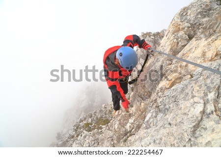 "Woman climbs via ferrata ""Punta Ana"" surrounded by clouds, Tofana massif, Dolomite Alps, Italy - stock photo"