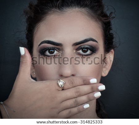woman closing her mouth with her hand - stock photo